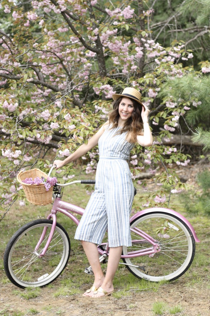 Blue and White Strip Jumpsuit with Boaters Hat with Jack Rogers Hampton Flip Flops on a Pink Cruiser Bike with fresh lilacs